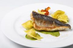 Белый и желтый равиоли рыб в зеленом соусе на плите на белом b стоковая фотография