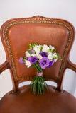 Белый и фиолетовый bridal букет на коричневом стуле Стоковая Фотография
