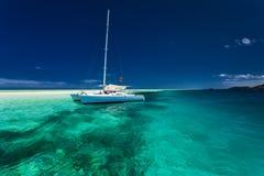 Белый катамаран в отмелой тропической воде с snorkeling рифом Стоковое Фото