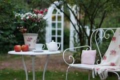 Белый комплект фарфора для чая или кофе на таблице в саде над предпосылкой природы зеленого цвета нерезкости, малой глубиной поля Стоковое Изображение RF