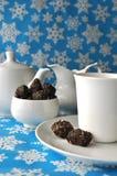 Белый комплект чая с помадками грецкого ореха и даты шоколада на голубой предпосылке зимы Стоковые Изображения RF