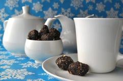 Белый комплект чая с помадками грецкого ореха и даты шоколада на голубой предпосылке зимы Стоковое Изображение