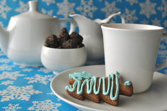 Белый комплект чая с помадками печенья меда рождества и грецкого ореха и даты шоколада на голубой предпосылке зимы с снежинками Стоковое фото RF