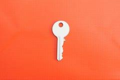Белый ключ на оранжевом кирпиче Стоковое фото RF