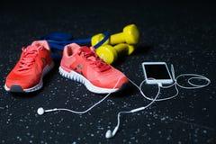 Белый мобильный телефон с наушниками, розовыми тапками, 2 желтыми гантелями и детандером на запачканной предпосылке Стоковые Изображения RF