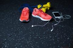 Белый мобильный телефон с наушниками, розовыми тапками, 2 желтыми гантелями и детандером на запачканной предпосылке Стоковые Фото