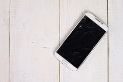 Белый мобильный телефон с сломленным экраном на деревянной предпосылке Стоковые Фото