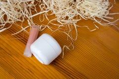 Белый опарник с сливк и губная помада лежат на деревянном столе Стоковая Фотография RF
