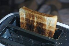 Белый пакостный тостер и, который сгорели здравица (селективный фокус, темный тон) Стоковая Фотография RF
