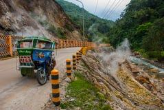 Белый пар от горы вулкана и пересекает дорогу с мотоциклом с sidecar philippines Валенсия, Ne острова стоковые изображения
