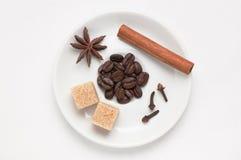 Белый поддонник с кофейными зернами, специями и тростниковым сахаром против белой предпосылки, взгляд сверху с местом для текста Стоковая Фотография
