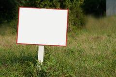 Белый пустой знак с красной доской в лесе, парке или саде лета Стоковая Фотография