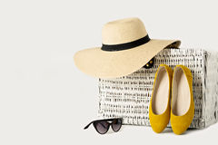 Белый плетеный чемодан, шляпа женщин, солнечные очки и желтые ботинки Стоковое Изображение RF