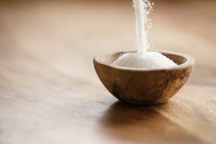 Белый сахар падая в деревянный шар на таблице Стоковое фото RF