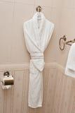 Белый свежий вид робы ванны на стене ванной комнаты Белая мантия ливня и малые полотенца висят в стене плиток камня ванной комнат Стоковые Изображения RF