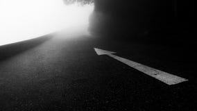 Белый символ стрелки на дороге горного склона Стоковое Фото