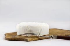 Белый сыр на белизне изолировал предпосылку на прерывая доске стоковые изображения