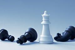 Белый ферзь шахмат и черные формы на свете - голубой предпосылке Стоковое фото RF