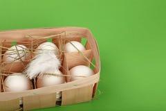 Белый цыпленок eggs в деревянном контейнере над зеленым цветом Стоковые Изображения RF
