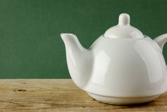 Белый чайник на старом деревянном столе Стоковая Фотография RF