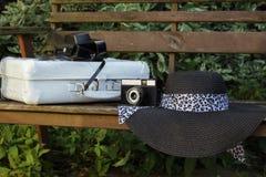 Белый чемодан, старая камера и шляпа на стенде в саде Стоковые Изображения