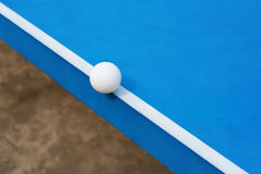 Белый шарик пингпонга ударяет край голубой таблицы пингпонга стоковые фотографии rf