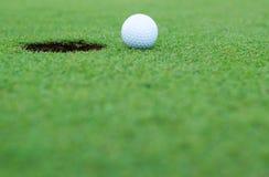 Белый шар для игры в гольф на зеленом цвете установки Стоковое фото RF