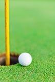 Белый шар для игры в гольф на зеленом цвете установки стоковые изображения