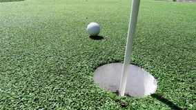 Белый шар для игры в гольф ударяя ручку флага и падая в отверстие на зеленом цвете установки видеоматериал