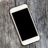 Белый smartphone с черным экраном на деревенской предпосылке тимберса Стоковые Изображения RF