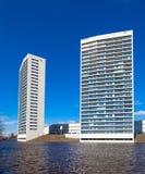 2 белых башни квартиры на фронте воды с голубым небом Стоковая Фотография