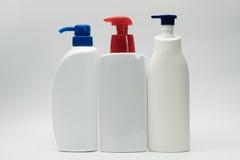 3 белых бутылки с красным и голубым насосом Стоковое Изображение