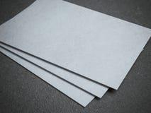 3 белых визитной карточки на сером поле Стоковые Фото