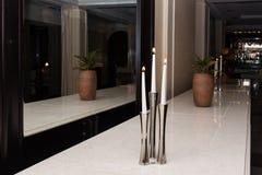 3 белых горящих свечи в железном подсвечнике Бак с растительностью Стоковое фото RF