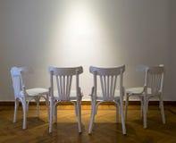 4 белых деревянных стуль смотря на белую стену на деревянном поле партера Стоковые Изображения