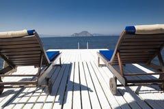 2 белых деревянных шезлонга на белой деревянной пристани морем Стоковое Изображение RF