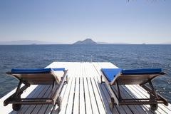 2 белых деревянных шезлонга на белой пристани agains моря Стоковые Фото