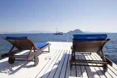 2 белых деревянных шезлонга на деревянной пристани agai моря Стоковые Изображения