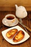 2 белых здравицы на белой плите с чашкой черного чая Стоковое Фото
