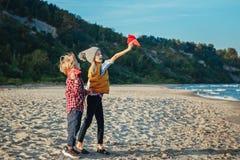 2 белых кавказских дет детей, более старой сестра и младший брат играя бумажные самолеты на пляже моря океана на заходе солнца ou Стоковые Фото
