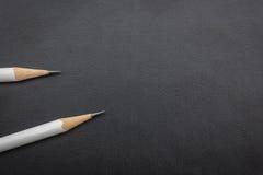 2 белых карандаша на черноте Стоковое Изображение