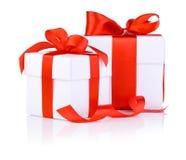 2 белых коробки связанной с красной лентой сатинировки обхватывают Стоковая Фотография