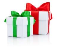 2 белых коробки связали красную и зеленые ленты обхватывают изолированный на белизне Стоковая Фотография