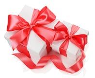 2 белых коробки связали красный смычок ленты на белизне Стоковые Фото