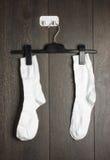 2 белых носка повешенного на стене Стоковое Фото