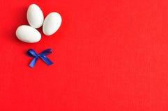 3 белых пасхального яйца с голубым смычком Стоковое Изображение