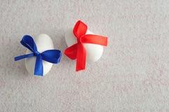 2 белых пасхального яйца с смычками другого цвета Стоковое Изображение RF