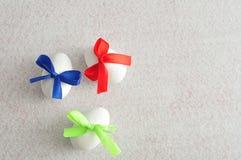 3 белых пасхального яйца с смычками другого цвета Стоковые Фотографии RF