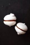 2 белых печенья меренги с шоколадом на черной предпосылке Стоковое фото RF