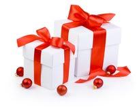 2 белых подарочной коробки связали красную изолированные ленту и шарики рождества Стоковые Изображения